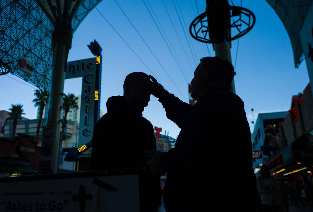 Steve Willis, a senior pastor at First Christian Church, right, marks the forehead of Bishop Williams of Las Vegas for Ash Wednesday on Fremont Street in downtown Las Vegas on Wednesday, Feb. 14,  ...