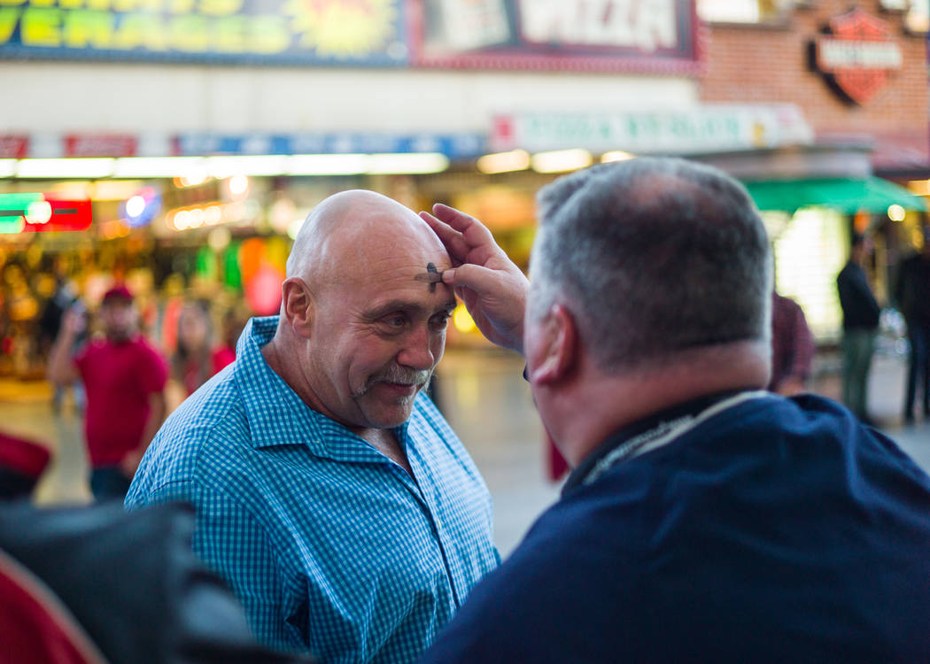 Steve Willis, a senior pastor at First Christian Church, right, marks the forehead of Frank Cormier of New Brunswick, Canada for Ash Wednesday on Fremont Street in downtown Las Vegas on Wednesday, ...