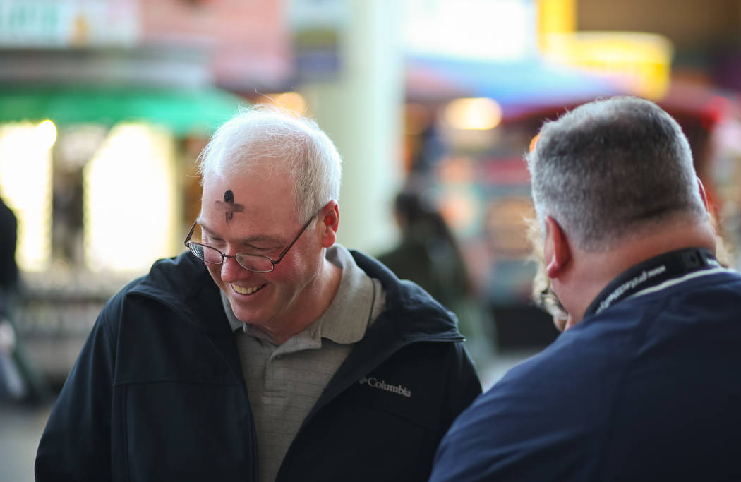 Alan Heitz of Iowa, left, after getting his forehead marked by Steve Willis, a senior pastor at First Christian Church, for Ash Wednesday on Fremont Street in downtown Las Vegas on Wednesday, Feb. ...