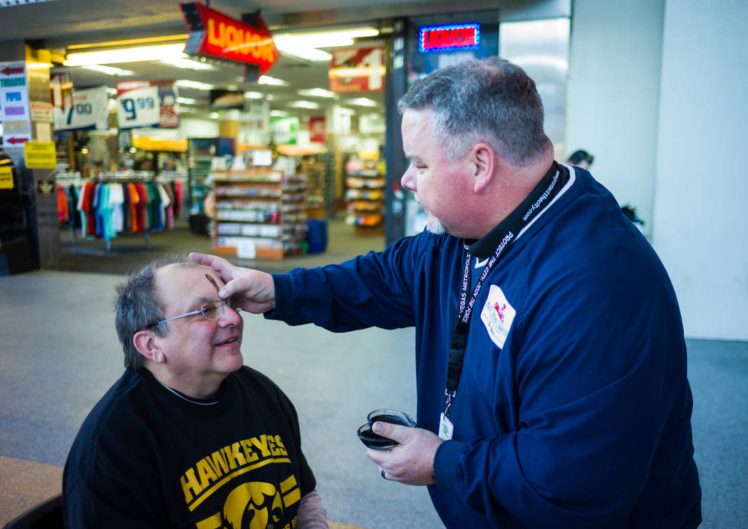 Steve Willis, a senior pastor at First Christian Church, right, marks the forehead of Sam Adam of Iowa City, Iowa for Ash Wednesday on Fremont Street in downtown Las Vegas on Wednesday, Feb. 14, 2 ...