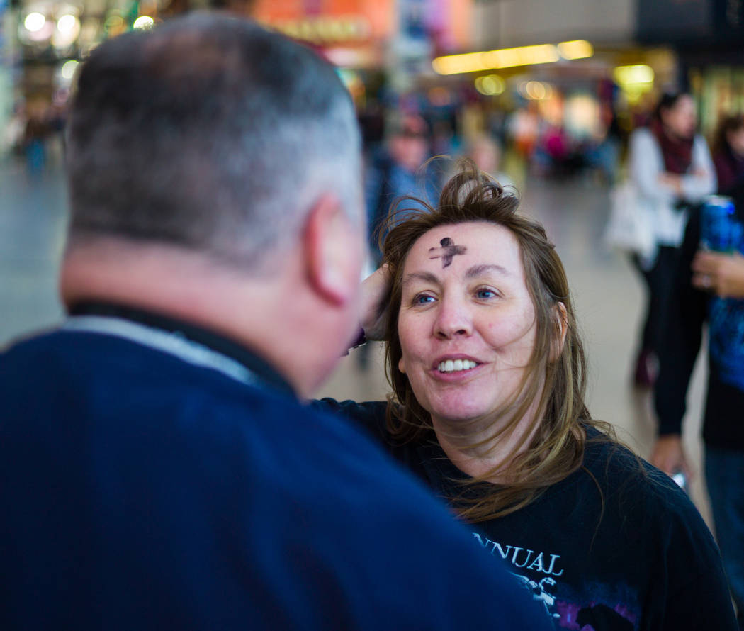 Steve Willis, a senior pastor at First Christian Church, marks the forehead of Michelle Caldwell of Ill. for Ash Wednesday on Fremont Street in downtown Las Vegas on Wednesday, Feb. 14, 2018. Ash  ...