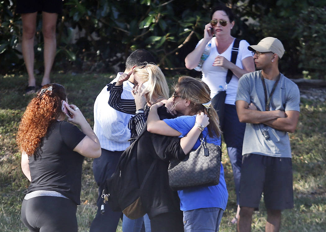 Anxious family members wait for news of students as two people embrace, Wednesday, Feb. 14, 2018, in Parkland, Fla. A shooting at Marjory Stoneman Douglas High School sent students rushing into th ...
