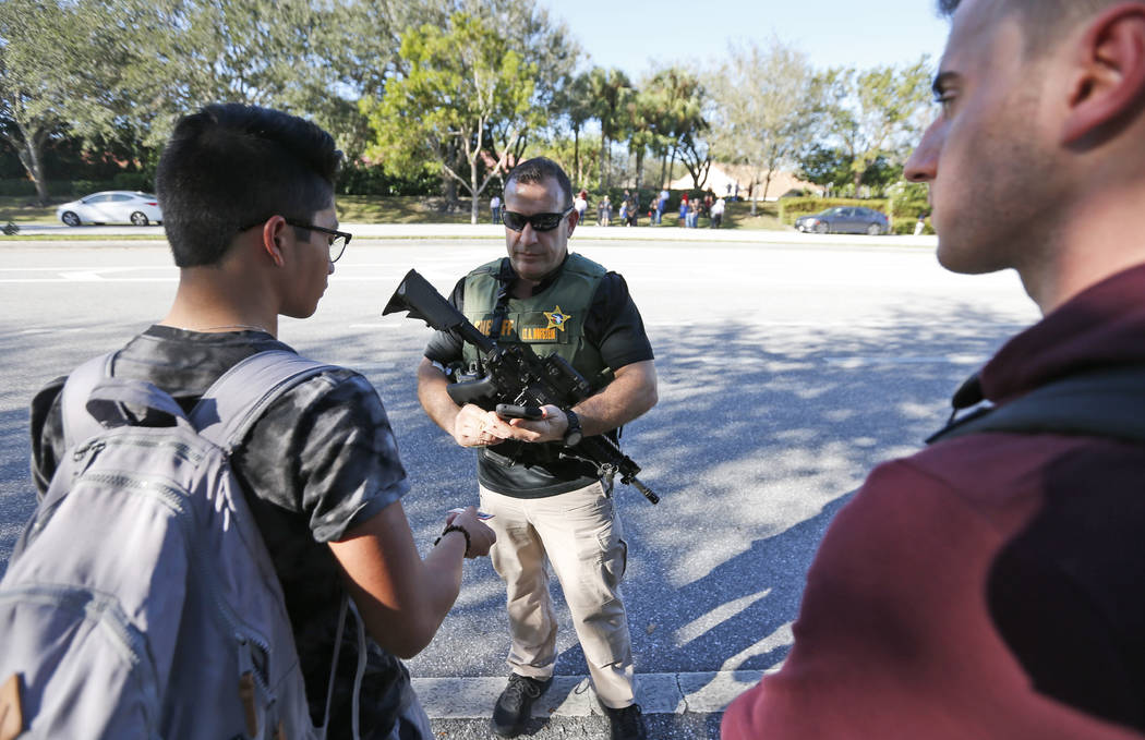 A law enforcement officer talks with students, Wednesday, Feb. 14, 2018, in Parkland, Fla. A shooting at Marjory Stoneman Douglas High School sent students rushing into the streets as SWAT team me ...