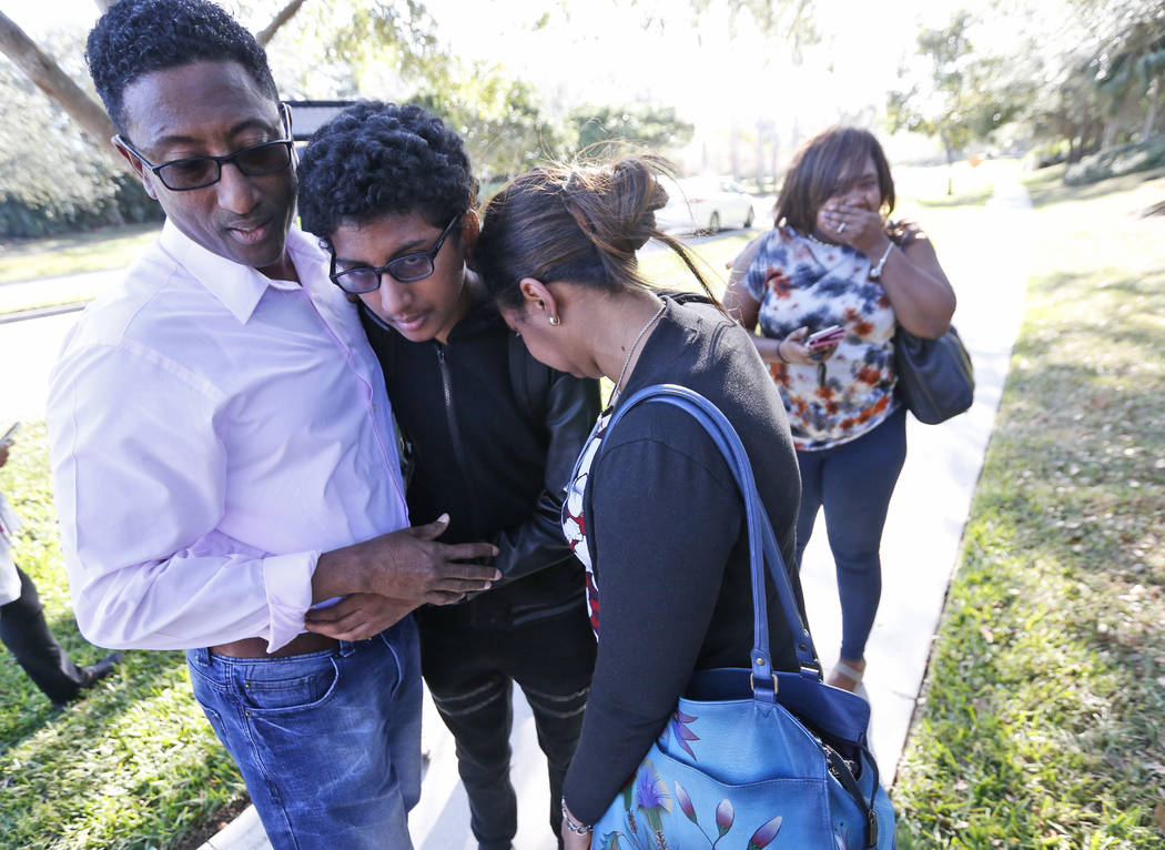 Family members embrace after a student walked out from Marjory Stoneman Douglas High School, Wednesday, Feb. 14, 2018, in Parkland, Fla. The shooting at the South Florida high school sent students ...