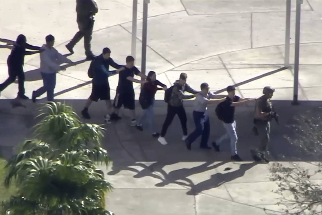 In this frame grab from video provided by WPLG-TV, students from the Marjory Stoneman Douglas High School in Parkland, Fla., evacuate the school following a shooting, Wednesday, Feb. 14, 2018. (WP ...