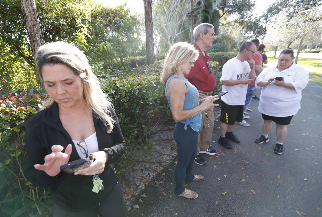 Anxious family members wait for information on students, Wednesday, Feb. 14, 2018, in Parkland, Fla. A shooting at Marjory Stoneman Douglas High School sent students rushing into the streets as SW ...