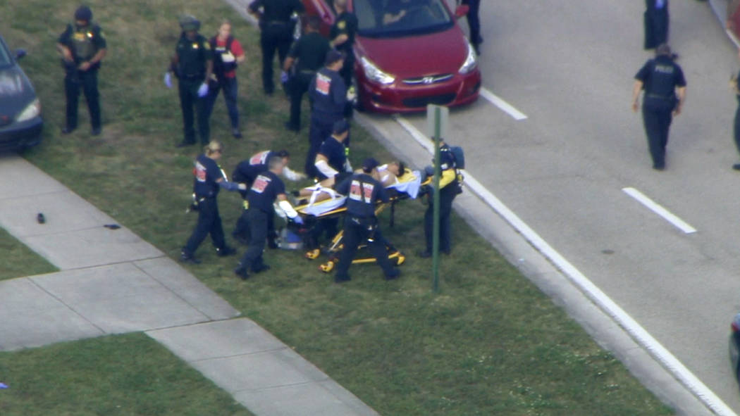In this frame grab from video provided by WPLG-TV, emergency personnel wheel an injured person from the Marjory Stoneman Douglas High School in Parkland, Fla., following a shooting there on Wednes ...