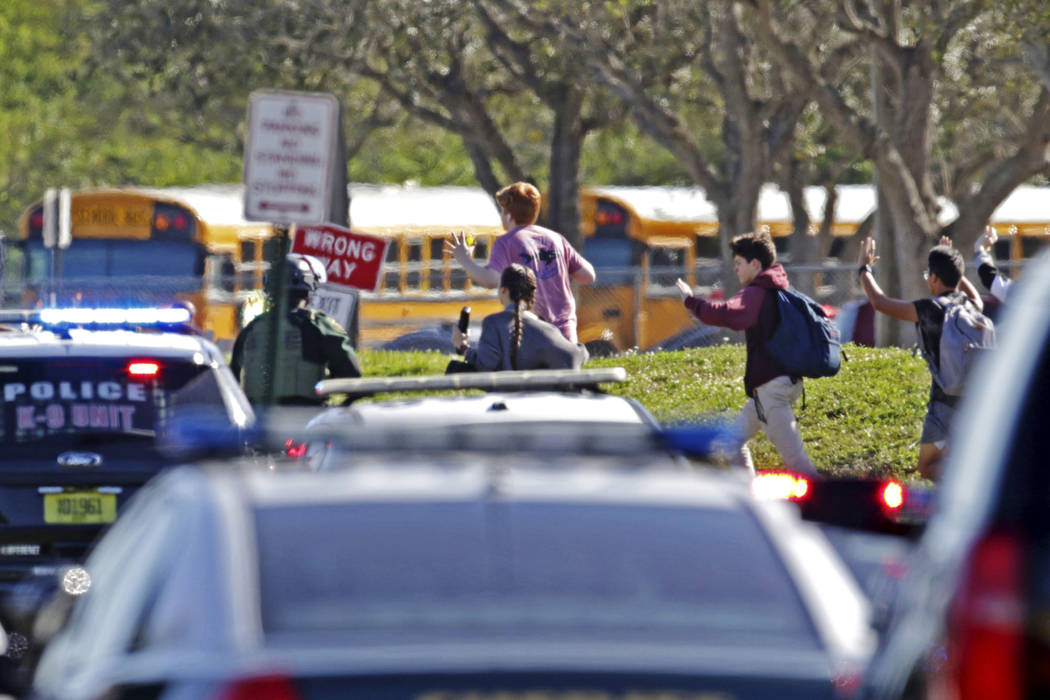 Students run with their hands in the air following a shooting at Marjory Stoneman Douglas High School in Parkland, Fla., Wednesday, Feb. 14, 2018. (John McCall/South Florida Sun-Sentinel via AP)