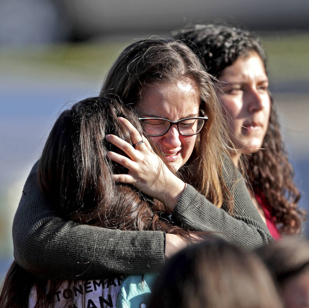 Students released from a lockdown embrace following following a shooting at Marjory Stoneman Douglas High School in Parkland, Fla., Wednesday, Feb. 14, 2018. (John McCall/South Florida Sun-Sentine ...