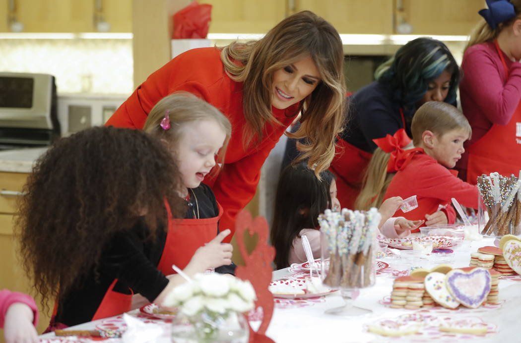 First lady Melania Trump meets with children making cookies for Valentine's Day during her visit to the Children's Inn at the National Institute of Health, Wednesday, Feb. 14, 2018, in Bethesda, M ...