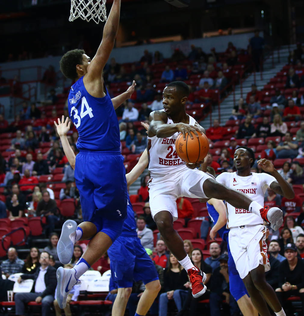 UNLV Rebels guard Jordan Johnson (24) throws a pass around Air Force Falcons forward Ryan Swan (34) during a basketball game at the Thomas & Mack Arena in Las Vegas on Wednesday, Feb. 14, 2018 ...