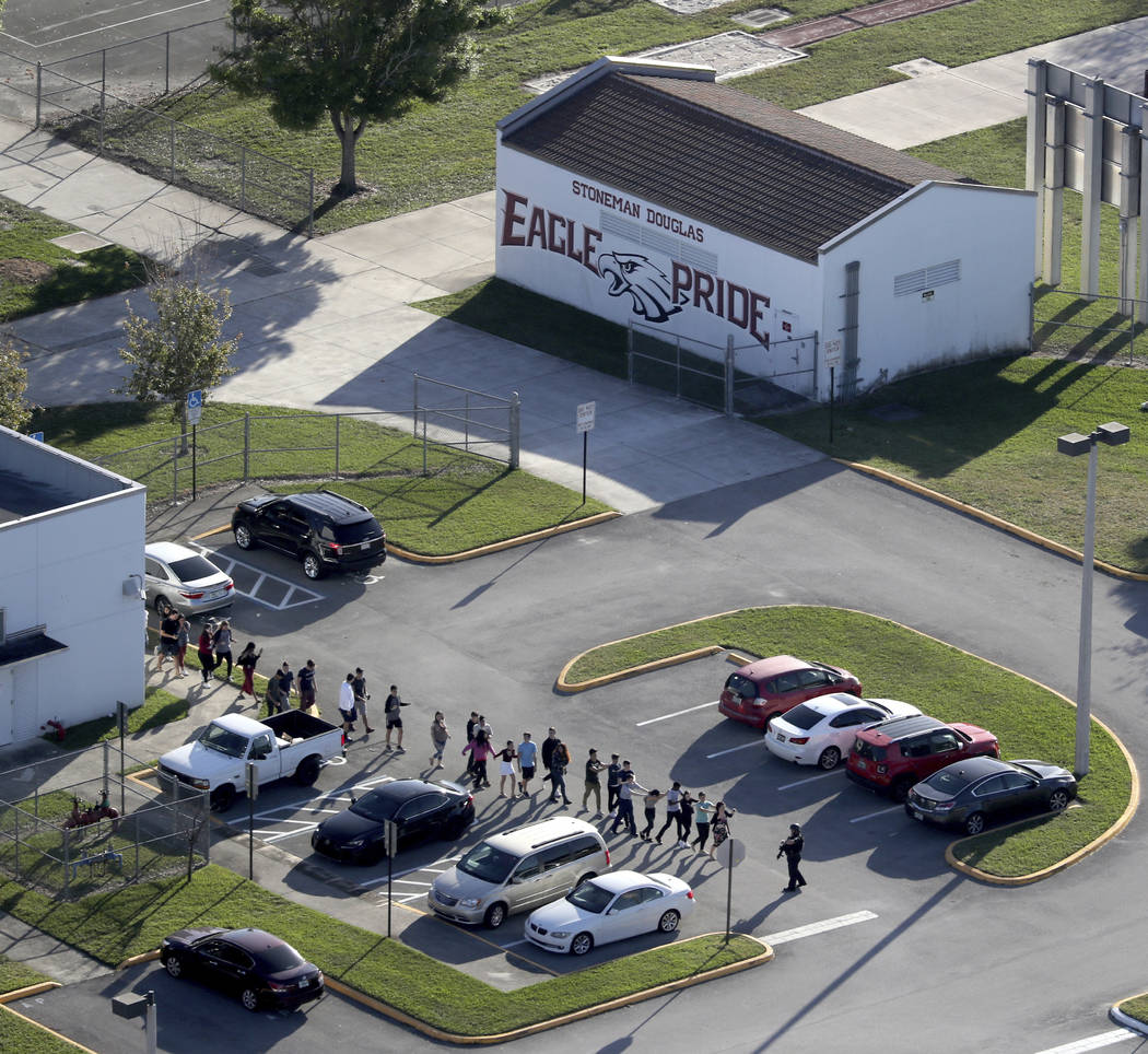 CORRECTS SPELLING TO MARJORY NOT MARJORIE Students are evacuated by police from Marjory Stoneman Douglas High School in Parkland, Fla., on Wednesday, Feb. 14, 2018, after a shooter opened fire on  ...