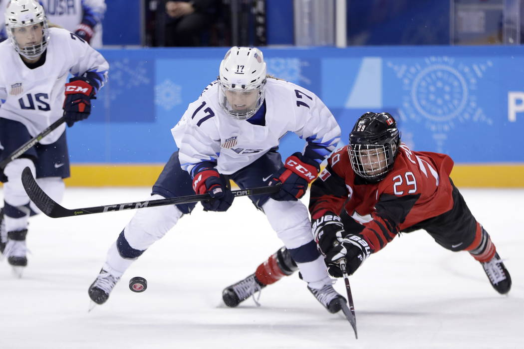 Jocelyne Lamoureux-Davidson (17), of the United States, and Marie-Philip Poulin (29), of Canada, compete for the puck during the second period of a preliminary round during a women's hockey game a ...