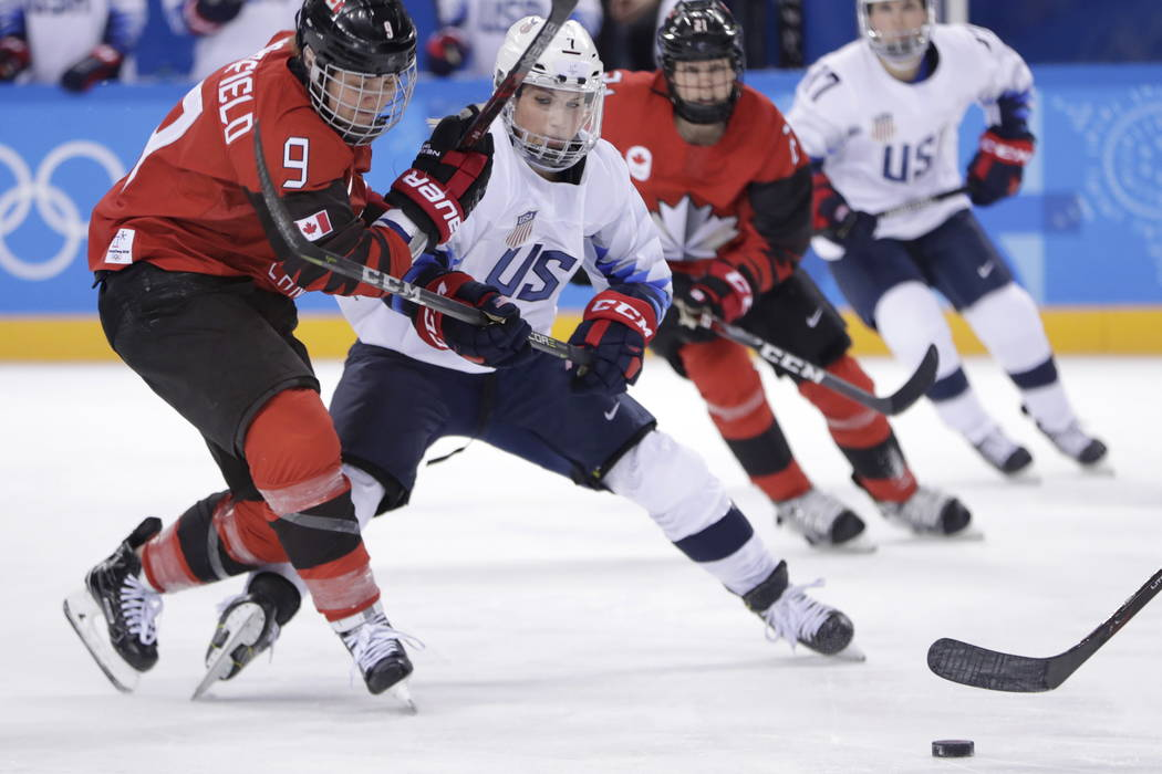 Jennifer Wakefield (9), of Canada, and Monique Lamoureux-Morando (7), of the United States, compete for the puck during the second period of a preliminary round during a women's hockey game at the ...