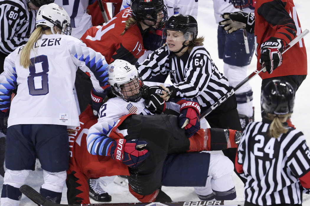 Official Jenni Heikkinen (64), of Finland, tries to separate Kelly Pannek (12), of the United States, and Laura Stacey (7), of Canada, as they scuffle during the third period of a preliminary roun ...