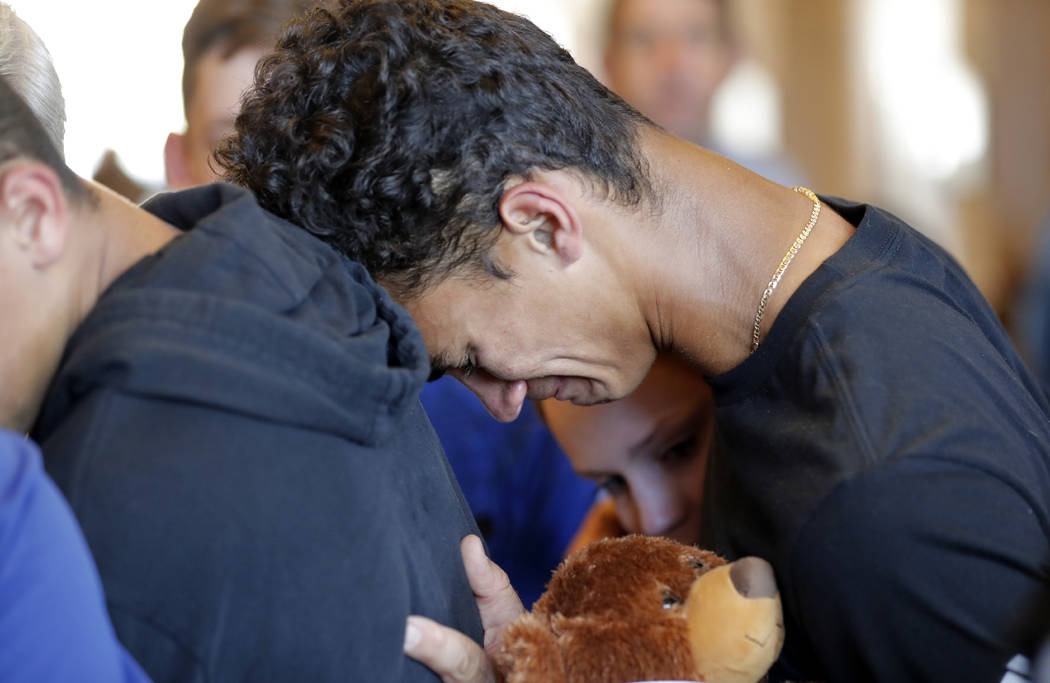 Austin Burden, 17, cries on the shoulder of a friend after a vigil at the Parkland Baptist Church, for the victims of the Wednesday shooting at Marjory Stoneman Douglas High School, in Parkland, F ...