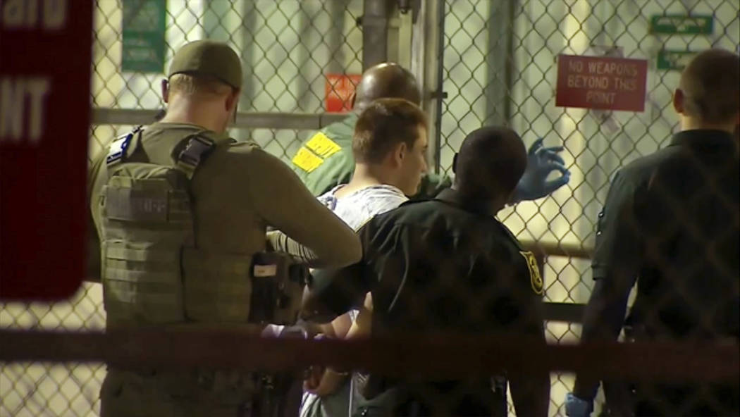 In this frame grab from video provided by WPLG-TV,  police take Nikolas Cruz into Broward County jail on Thursday, Feb. 15, 2018 in Fort Lauderdale, Fla.  Cruz was charged with 17 counts of premed ...