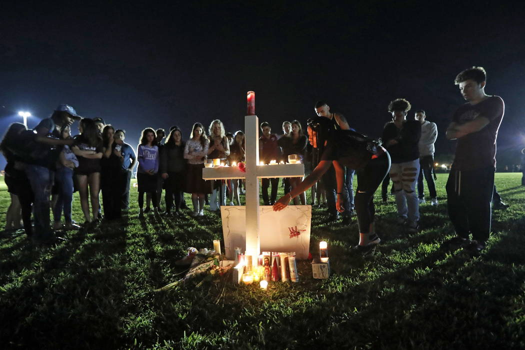 A woman places a poster of shooting victim Meadow Pollack, at one of seventeen crosses, after a candlelight vigil for the victims of the Wednesday shooting at Marjory Stoneman Douglas High School, ...