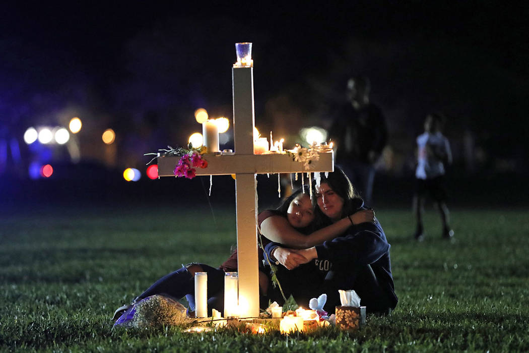 Two people comfort each other as they sit and mourn at one of seventeen crosses, after a candlelight vigil for the victims of the Wednesday shooting at Marjory Stoneman Douglas High School, in Par ...