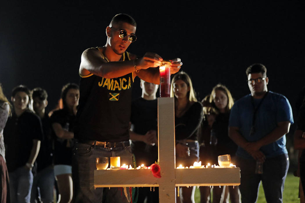 Joey Kandil, 18, a recent graduate of Marjory Stoneman Douglas High School, places a ring around a candle on one of seventeen crosses, after a candlelight vigil for the victims of the Wednesday sh ...
