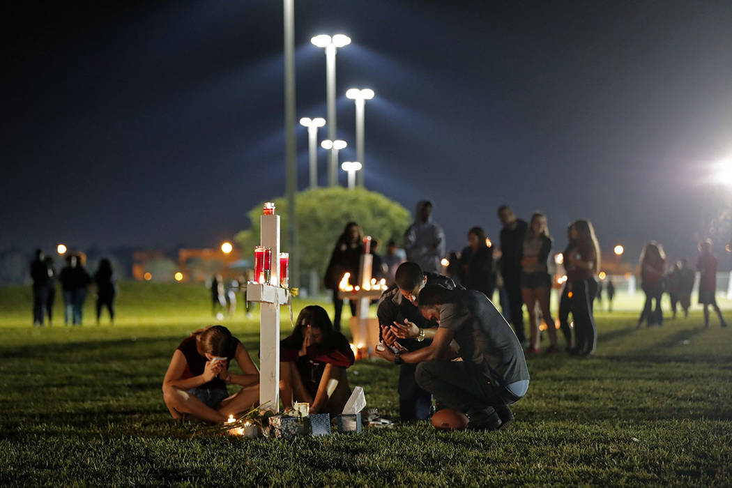 People pray around one of seventeen crosses, after a candlelight vigil for the victims of the Wednesday shooting at Marjory Stoneman Douglas High School, in Parkland, Fla., Thursday, Feb. 15, 2018 ...