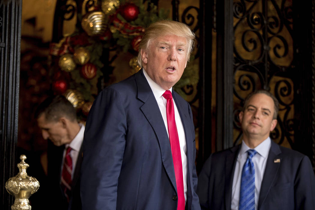 President-elect Donald Trump, center, accompanied by Trump Chief of Staff Reince Priebus, right, and retired Gen. Michael Flynn, a senior adviser to Trump, left, speaks to members of the media on  ...