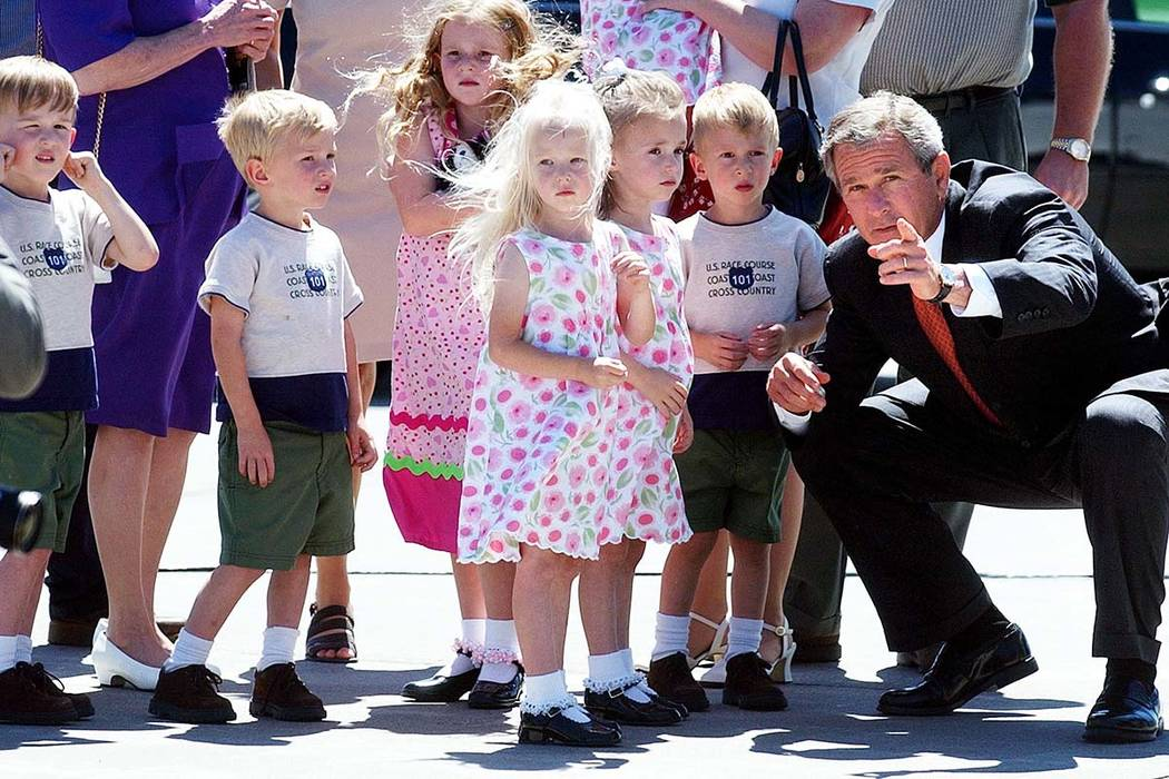 In this Aug. 14, 2002 file photo, President George W. Bush points out reporters and photographers to six of the McCaughey septuplets who greeted him on his arrival at the Des Moines International  ...
