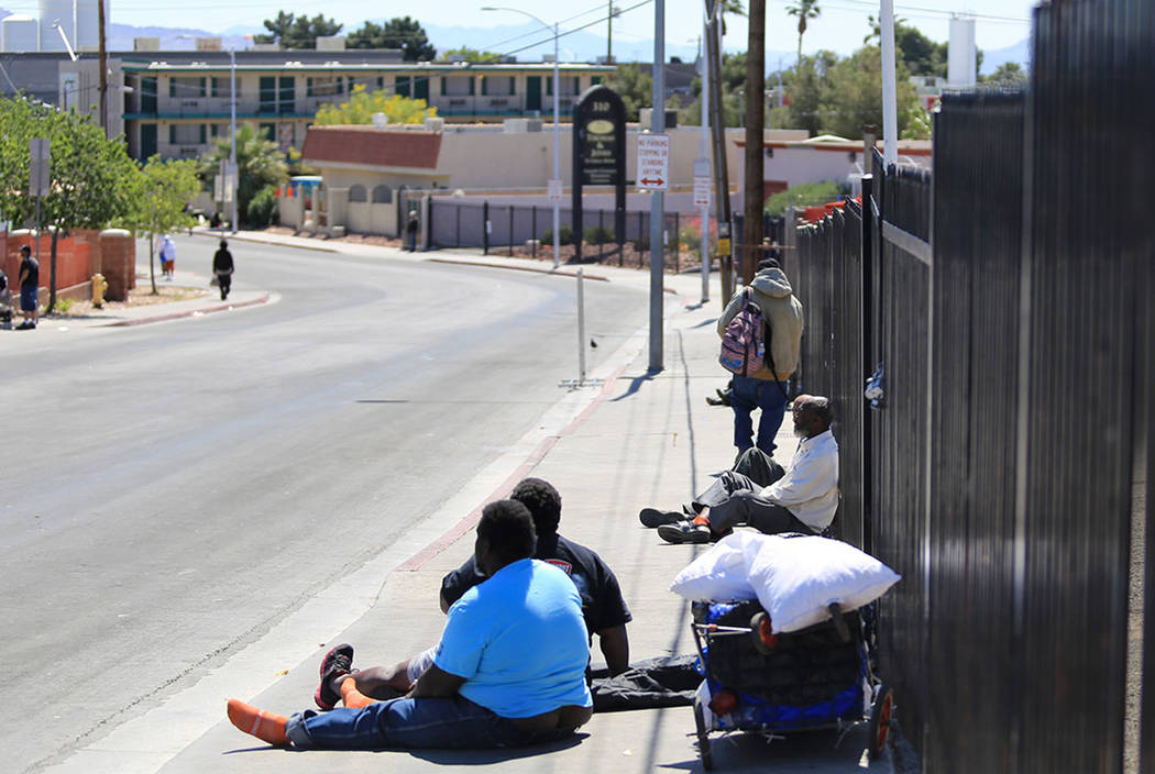 People sit on Foremaster Lane in Las Vegas, on Friday, April 28, 2017, in front of land that the city of Las Vegas is going to turn into a campus that will bring homeless providers together and gi ...