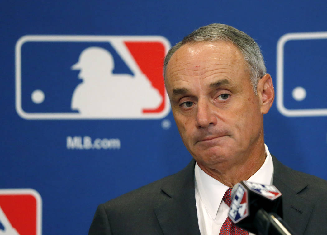 In this Aug. 17, 2017, file photo, Commissioner Rob Manfred listens to a question following the two-day meeting of Major League Baseball owners in Chicago. (AP Photo/Charles Rex Arbogast, File)