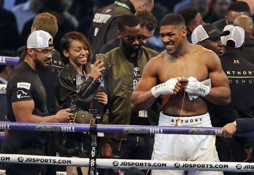 British boxer Anthony Joshua, right, smiles as he celebrates after beating Ukrainian boxer Wladimir Klitschko in a fight for Joshua's IBF and the vacant WBA Super World and IBO heavyweight titles  ...