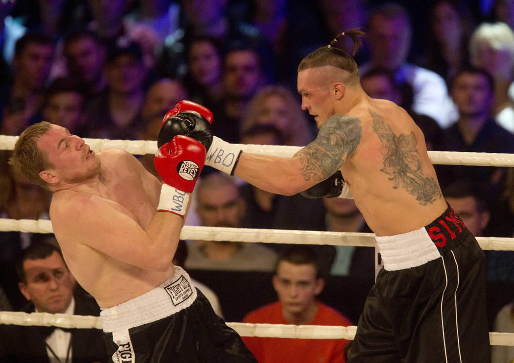 Ukrainian boxing Olympic champion Oleksandr Usyk, right, throws a punch to  Russia's Andrei Knyazev  during their WBO Inter-Continental heavyweight bout in Kiev, Ukraine, Saturday, April 18, 2015. ...