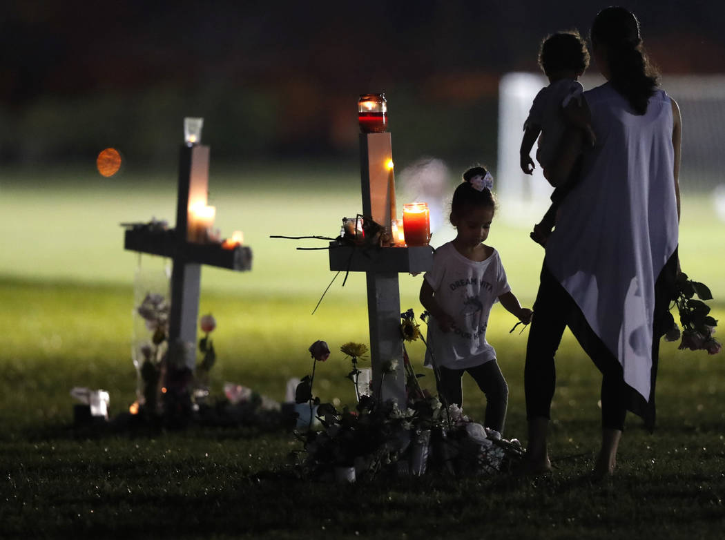 People pay homage at the memorial crosses, for the 17 deceased students and faculty from the Wednesday shooting at Marjory Stoneman Douglas High School, in Parkland, Fla., Friday, Feb. 16, 2018. N ...