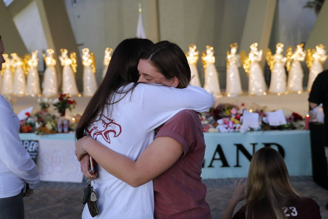 People hug at a public memorial for the 17 deceased students and faculty from Wednesday's shooting at Marjory Stoneman Douglas High School, in Parkland, Fla., Friday, Feb. 16, 2018. (AP Photo/Gera ...