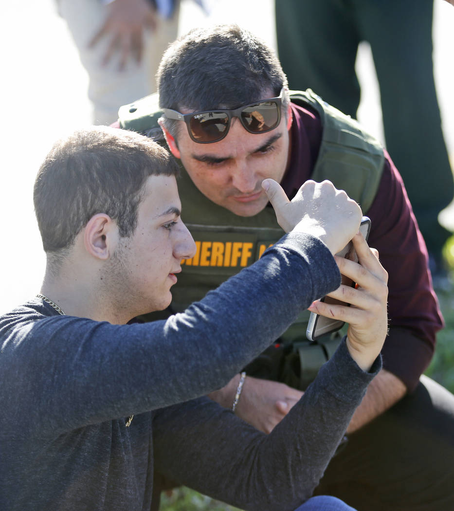 A student shows a law enforcement officer a photo or video from his phone, Wednesday, Feb. 14, 2018, in Parkland, Fla. A shooting at Marjory Stoneman Douglas High School sent students rushing into ...