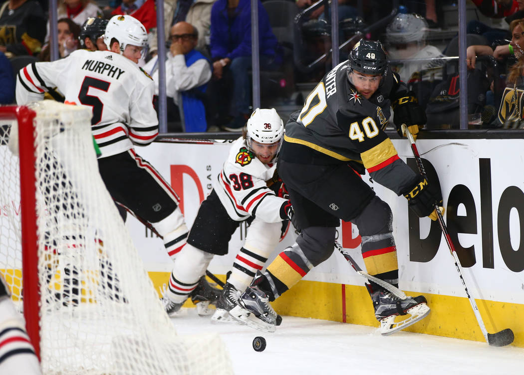 Golden Knights center Ryan Carpenter (40) looks to get the puck against Chicago Blackhawks left wing Ryan Hartman (38) and defenseman Connor Murphy (5) during an NHL game at T-Mobile Arena in Las  ...