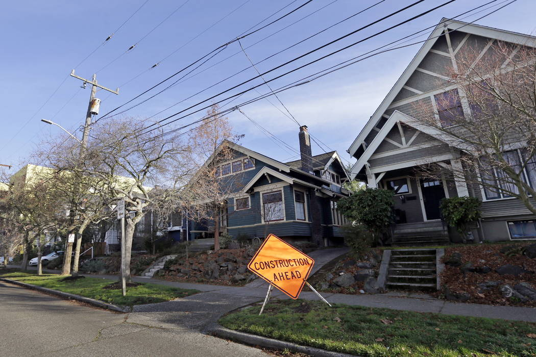 A four-story mixed-use building is under construction at the end of a street of older, single-family homes in Seattle in December. (AP Photo/Elaine Thompson)