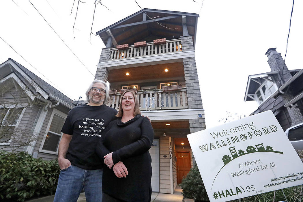 Bryan Kirschner, left, and his wife, Holly Ferguson, supporters of a proposed development plan, stand in front of their tall, narrow house, which sits adjacent to older, traditional homes, in Seat ...