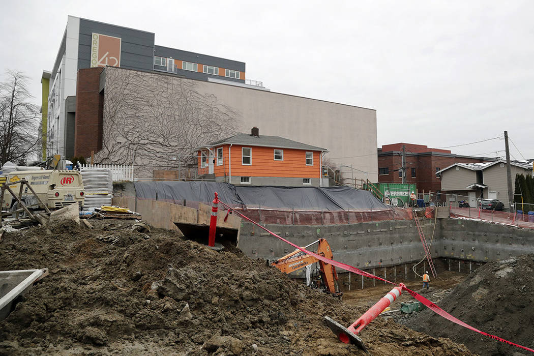 A single-family home remains on the edge of where a multi-story, mixed-use building is being constructed in Seattle in December. (AP Photo/Elaine Thompson)