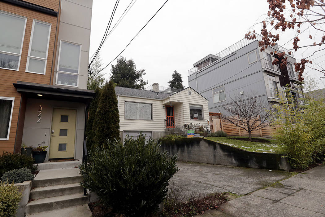 An older single-family home remains boxed-in between newer, multi-family homes in Seattle in December. (AP Photo/Elaine Thompson)