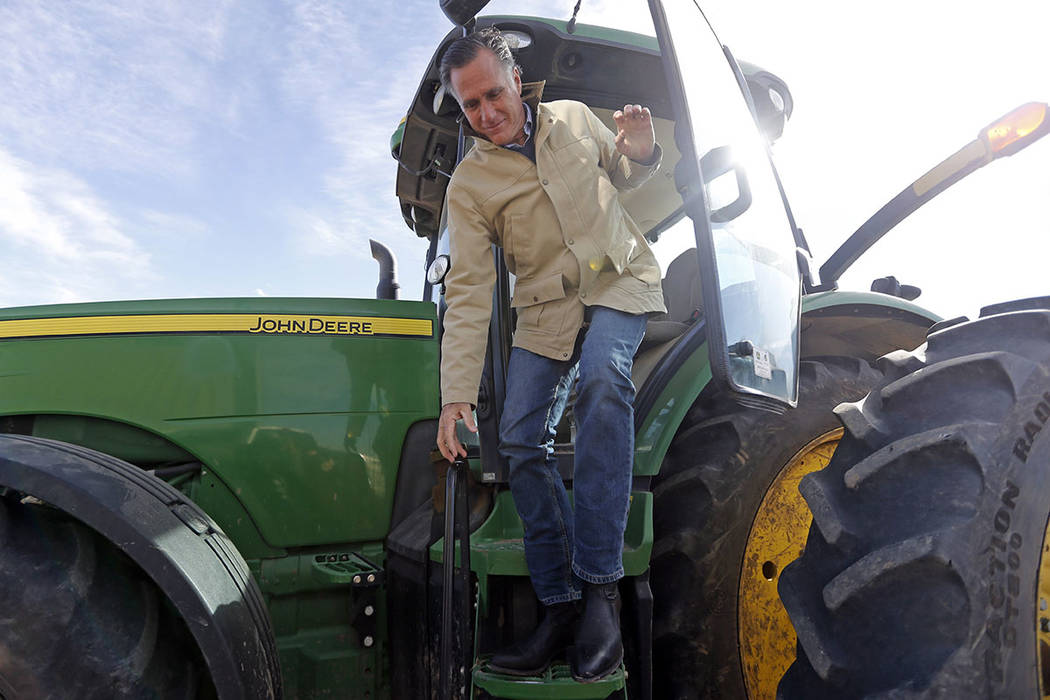 Former Republican presidential candidate Mitt Romney climbs down from a tractor during a tour of Gibson's Green Acres Dairy Friday, Feb. 16, 2018, in Ogden, Utah. (AP Photo/Rick Bowmer)