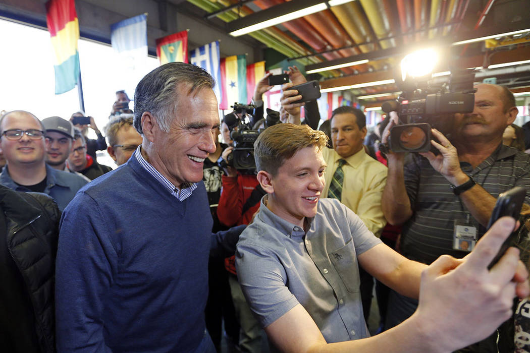 Former Republican presidential candidate Mitt Romney, left, poses for a photo as he greets students at Utah Valley University, Friday, Feb. 16, 2018, in Orem, Utah. (AP Photo/Rick Bowmer)