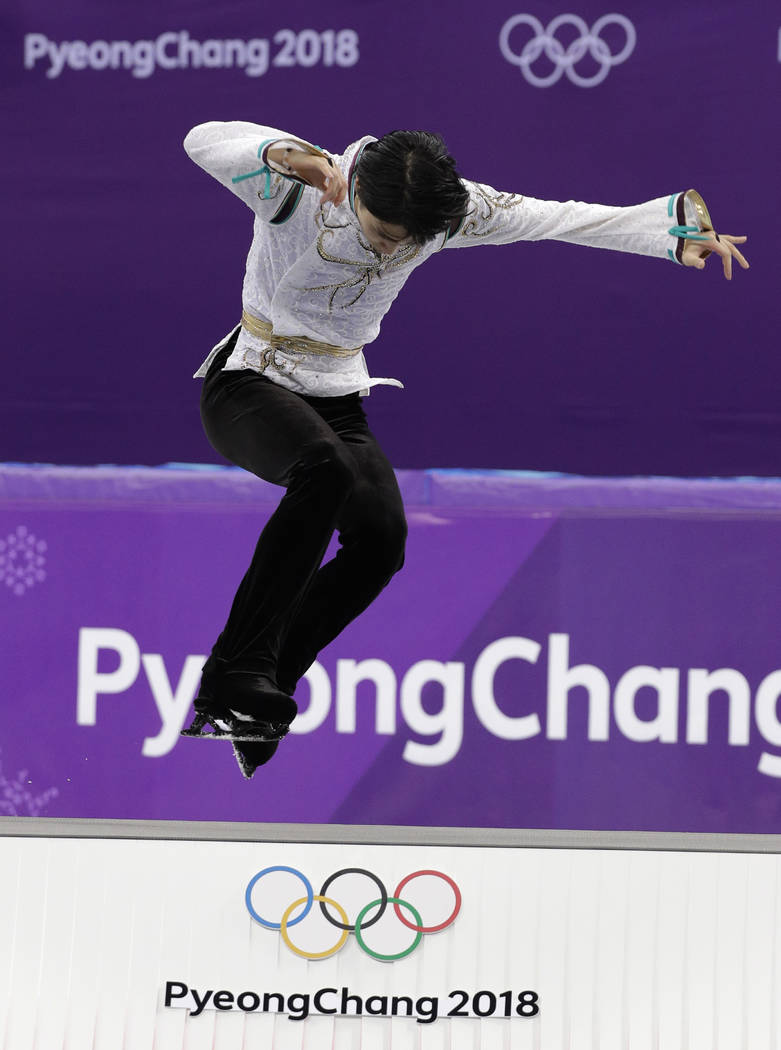 Yuzuru Hanyu of Japan leaps onto the podium as he celebrates his gold medal win in the the men's free figure skating final in the Gangneung Ice Arena at the 2018 Winter Olympics in Gangneung, Sout ...