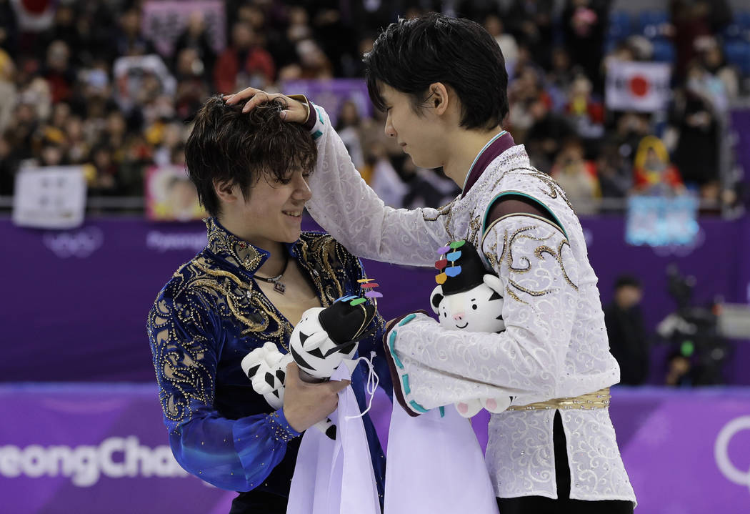 Gold medal winner Yuzuru Hanyu, right, of Japan reacts with teammate and silver medalist Shoma Uno after the men's free figure skating final in the Gangneung Ice Arena at the 2018 Winter Olympics  ...