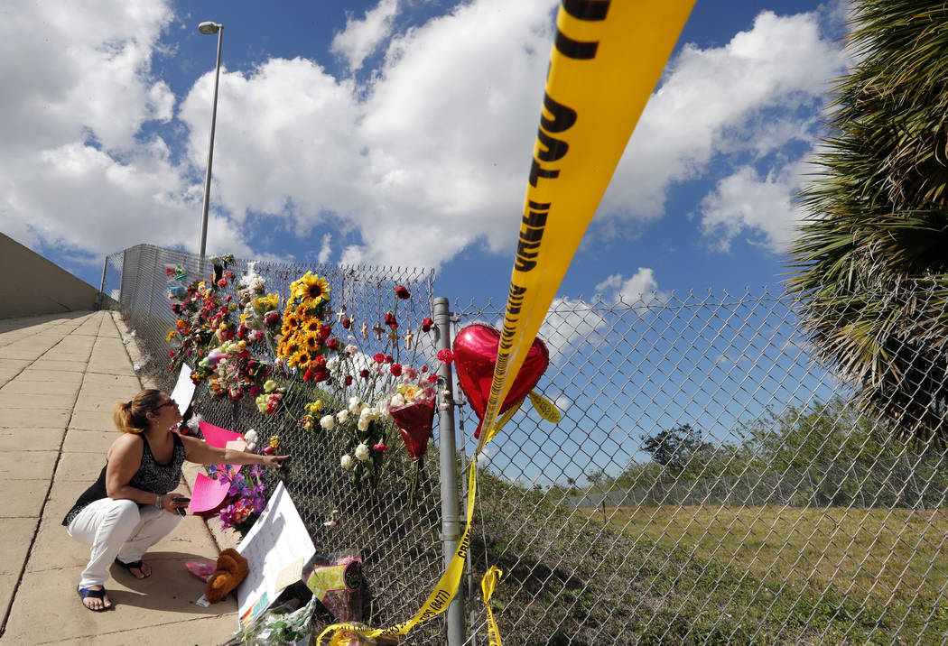 Carrie Hernandez, of Coral Springs, places flowers under an overpass, at the edge of the crime scene, near Marjory Stoneman Douglas High School, where students sought shelter after the Wednesday s ...