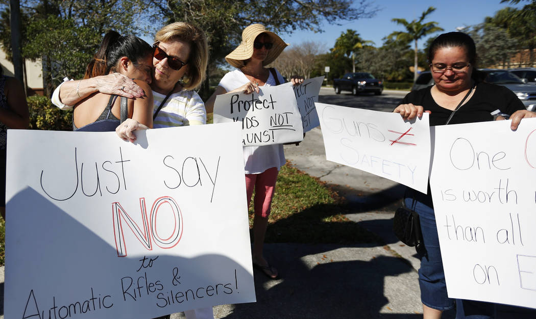 Cathy Kuhns, right, hugs Ana Paula Lopez, left, as they stands on a street corner holding up anti gun signs in Parkland, Fla., on Saturday, Feb. 17, 2018.  As families begin burying their dead, au ...