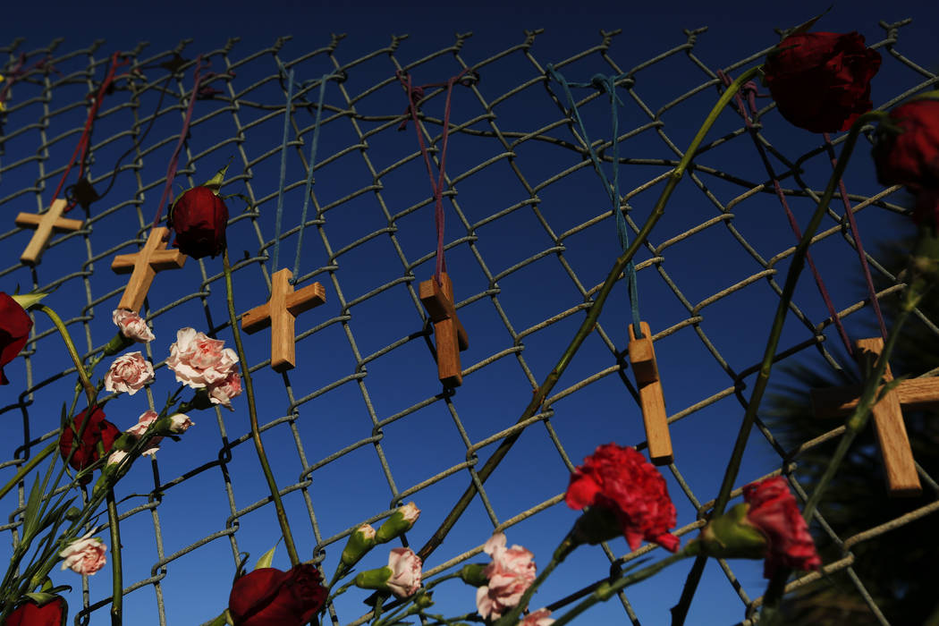 CORRECTS SPELLING OF SCHOOL NAME FROM MAJORITY STONEMAN DOUGLAS TO MARJORY STONEMAN - Crosses and flowers hang on a fence near  Marjory Stoneman Douglas  INParkland, Fla., on Saturday, Feb. 16, 20 ...