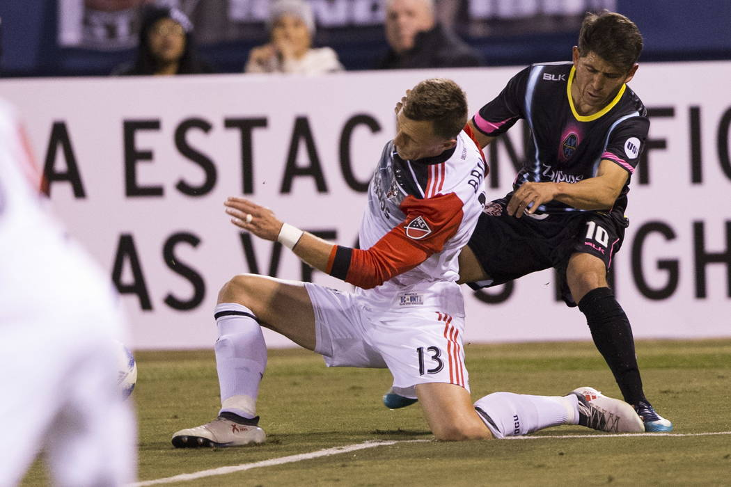 D.C. United's Frédéric Brillant (13) and Las Vegas Lights FC's Juan Jose Calderon (10) collide going to the ball during the first half of the exhibition soccer game at Cashman Fie ...
