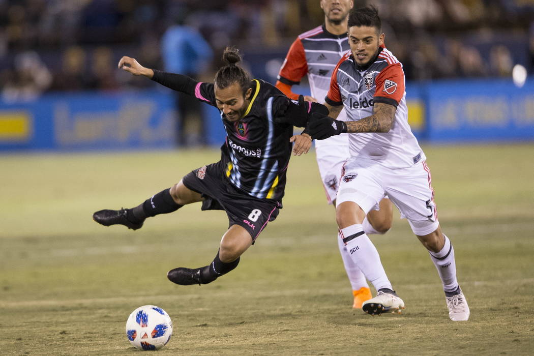 Las Vegas Lights FC's Isaac Diaz (8) is fouled by D.C. United's Junior Moreno (5) fight for the ball during the first half of the exhibition soccer game at Cashman Field in Las Vegas, Satur ...