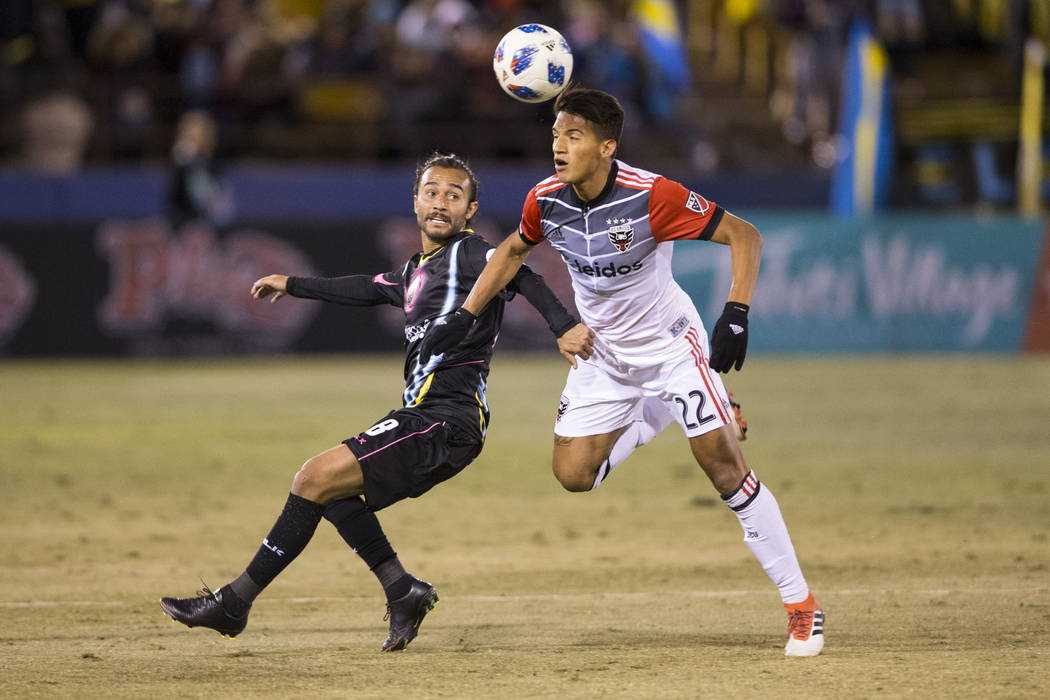 Las Vegas Lights FC's Isaac Diaz (8) and D.C. United Yamil Asad (22) go for the ball during the first half of the exhibition soccer game at Cashman Field in Las Vegas, Saturday, Feb. 24, 20 ...