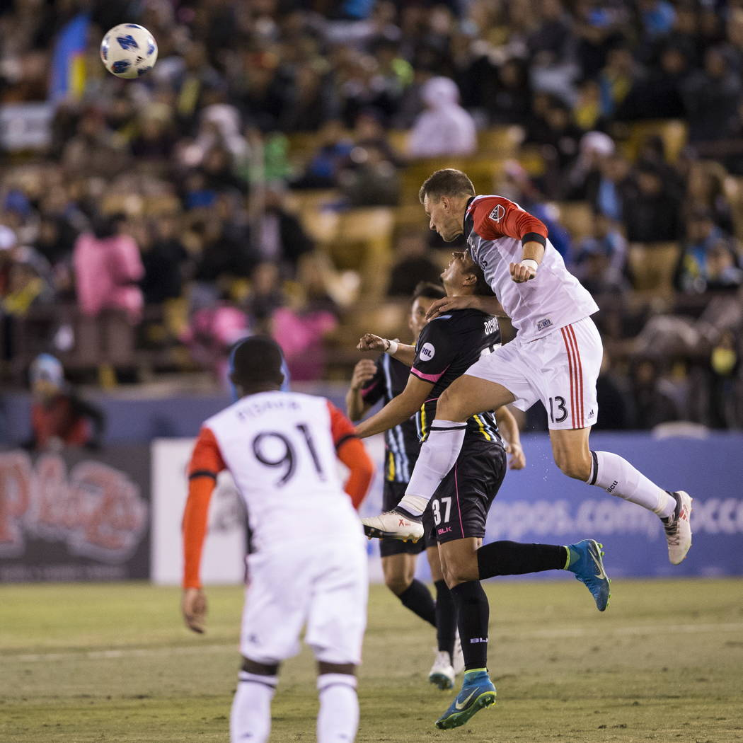 Las Vegas Lights FC's  Samuel Ochoa (37) and D.C. United Frédéric Brillant (13) leap for the ball during the first half of the exhibition soccer game at Cashman Field in Las Vegas ...
